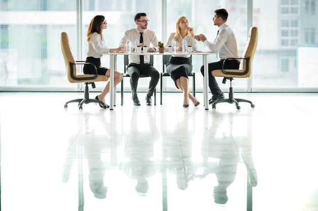 Auf der konferenz sitzen die geschäftsleute am tisch