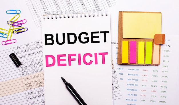 Auf der oberfläche der grafiken liegt ein notizbuch mit den worten budget deficit, ein marker, farbige büroklammern und helles notizpapier