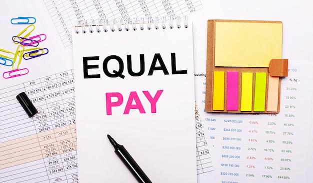 Auf der oberfläche der grafiken liegt ein notizbuch mit den worten equal pay, ein marker, farbige büroklammern und helles notizpapier.