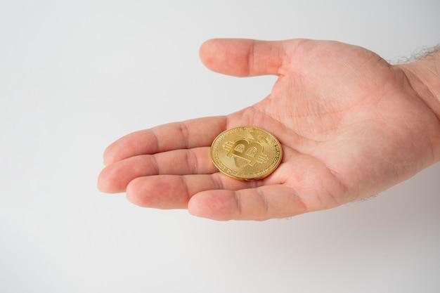 Auf der offenen männlichen handfläche befindet sich ein gold-bitcoin. weißer hintergrund. kryptowährungskonzept