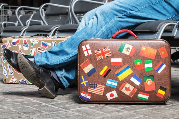 Auf der plattform steht ein koffer mit aufklebern aus aller welt