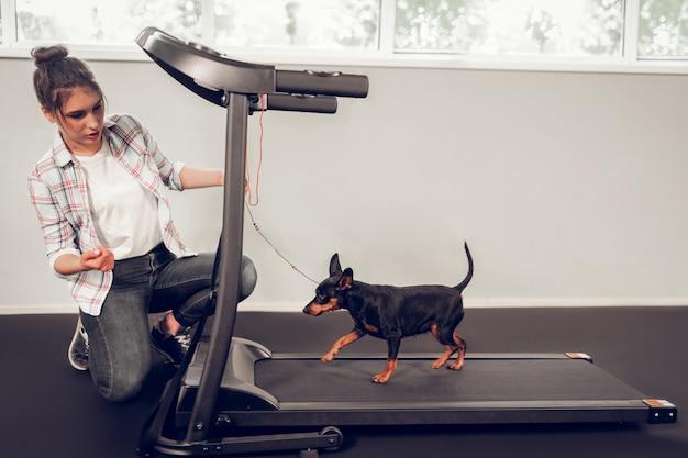 Auf der rennstrecke. dunkelhaariger besitzer eines schwarzen hundes, der das gefühl hat, ihn auf der rennstrecke zu trainieren