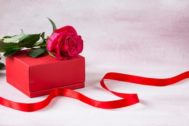 Auf der roten geschenkbox befindet sich eine rote rose und daneben ein rotes band