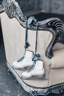 Auf der rückseite des sofas hängen weiße skates, die für eiskunstlauf verwendet werden