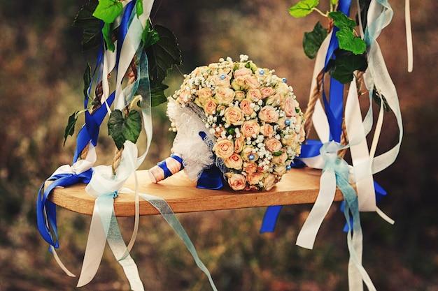 Auf der schaukel liegt ein hochzeitsstrauß aus pastellrosen mit blauen strasssteinen und band