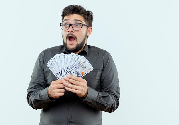 Auf der seite freudiger junger geschäftsmann, der brillen hält, die bargeld lokalisiert auf weißem hintergrund tragen