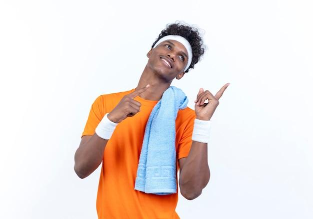 Auf der seite lächelnder junger afroamerikanischer sportlicher mann, der stirnband und armbandpunkte an der seite mit handtuch auf schulter trägt, lokalisiert auf weißem hintergrund mit kopienraum