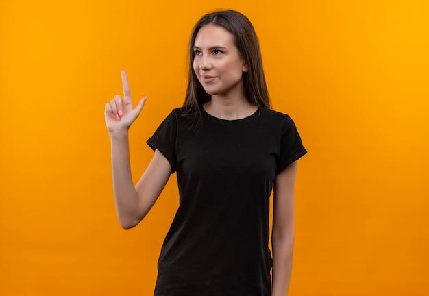 Auf der seite lächelndes junges kaukasisches mädchen, das schwarzes t-shirt trägt, zeigt nach oben mit finger auf isolierte orange wand