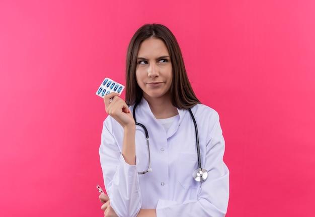 Auf der seite verwirrte junge ärztin, die das medizinische kleid des stethoskops hält, das pillen auf isolierter rosa wand hält