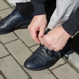Auf der straße ein mann bindet schnüre an schwarzen lederstiefeln
