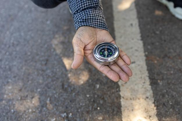 Auf der straße sucht die hand eines reisenden von einem kompass nach richtungen.