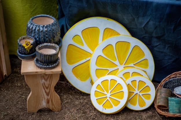 Auf der straßenmesse des festivals werden handgefertigte holzprodukte verkauft: blumentöpfe, hocker, dekorative elemente in form von gelben zitronen, kerzenhalter.