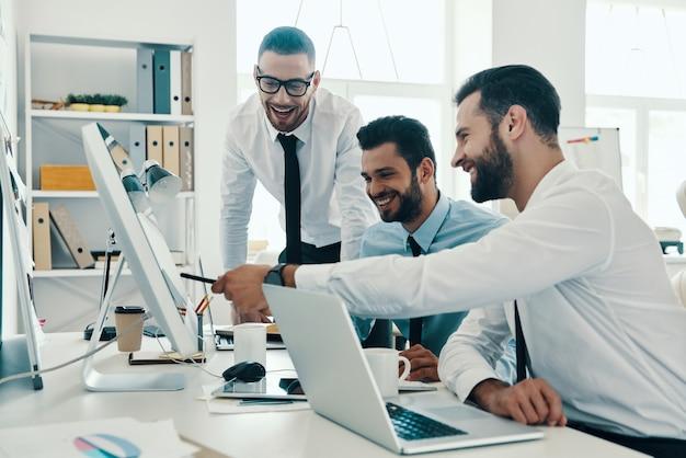 Auf der suche nach der richtigen entscheidung. gruppe junger moderner männer in formeller kleidung, die mit computern arbeiten, während sie im büro sitzen