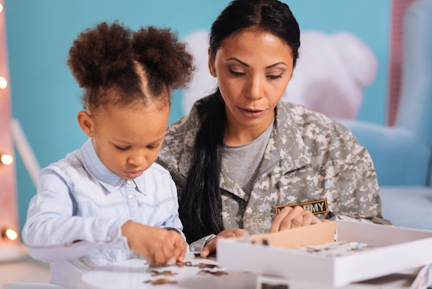 Auf der suche nach einem besonderen. unterstützende, inspirierende, wundervolle mutter, die die erforderlichen teile findet, um ein bild zu vervollständigen, während sie mit ihrem kind an ihrem kleinen weißen tisch sitzt