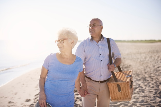 Auf der suche nach einem perfekten ort für ein picknick. älteres paar im strand-, ruhestands- und sommerferienkonzept