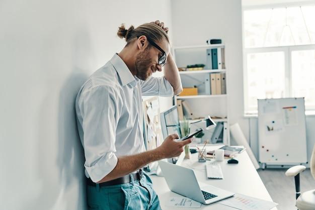 Auf der suche nach einer antwort. nachdenklicher junger mann im hemd mit smartphone beim stehen im büro