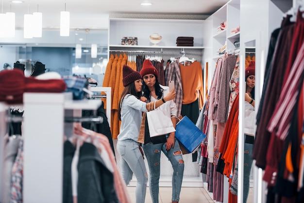 Auf der suche nach einer warmen kleidung. zwei junge frauen verbringen gemeinsam einen einkaufstag im supermarkt.