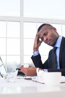 Auf der suche nach frischen ideen. hübscher junger afrikanischer geschäftsmann, der an seinem arbeitsplatz sitzt und den kopf in der hand hält