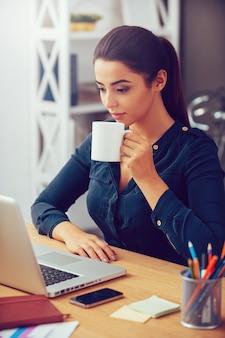 Auf der suche nach inspiration. attraktive junge frau, die kaffeetasse hält und laptop betrachtet