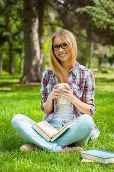 Auf der suche nach inspiration im freien. schöne junge studentin, die ihre brille justiert und lächelt, während sie in einem park mit büchern um sie herum sitzt?