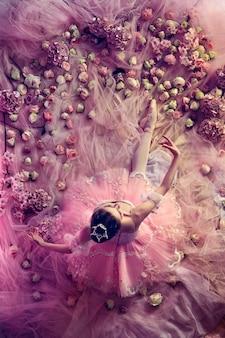 Auf der suche nach liebe. blick von oben auf die schöne junge frau im rosa ballett-ballettröckchen, umgeben von blumen. frühlingsstimmung und zärtlichkeit im korallenlicht. kunst foto. konzept des frühlings, der blüte und des erwachens der natur.