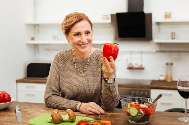 Auf der suche nach pfeffer. strahlende reife dame, die sich in der küche auf einen holztisch stützt und ganzen pfeffer präsentiert?