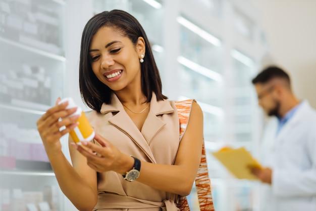 Auf der suche nach vitaminen. schöne dunkelhäutige frau, die positivität ausdrückt, während sie sich für eine neue medizin entscheidet