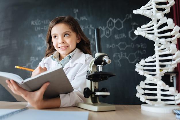 Auf der suche nach wissenschaftlicher inspiration. nachdenklicher positiver fröhlicher teenager, der im labor sitzt und naturwissenschaftlichen unterricht hat, während er studiert und notizen macht