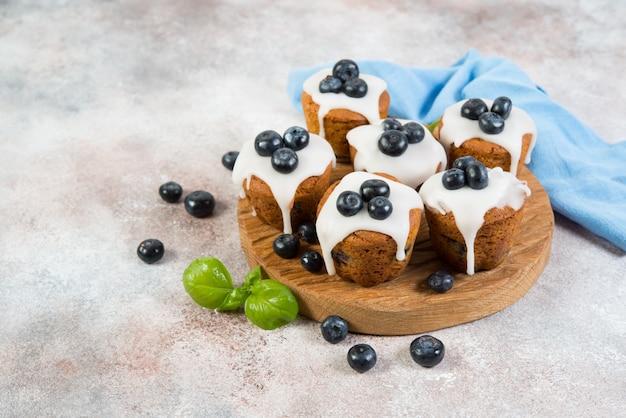 Auf der tafel rechts befinden sich köstliche vanillemuffins in zucker, fudge und blaubeeren. horizontales foto mit kopierraum.