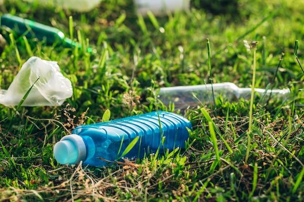 Auf der wiese abgelegte plastiktüten verunreinigen die umwelt. stapeln sie plastik- und glasflaschen auf grünem gras in den naturumweltproblemen. naturschutz.