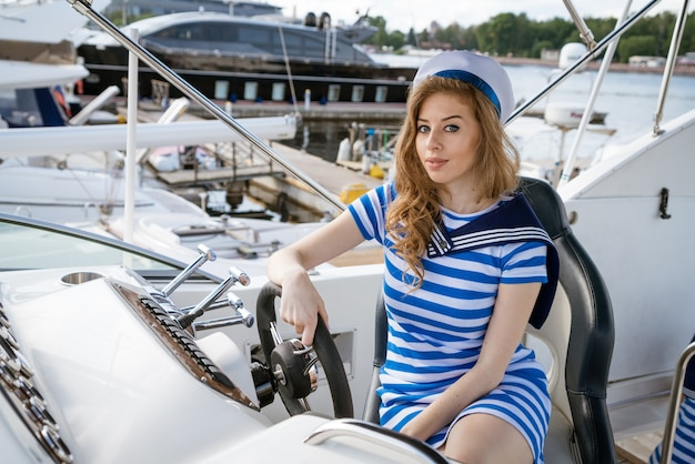Auf der yacht sitzt eine charmante blondine mit langen haaren in einem seestilkleid