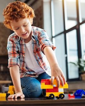 Auf die plätze, fertig, los. völlig in den prozess des spiels rothaariges kind vertieft konzentriert seine aufmerksamkeit auf ein gebautes plastikauto