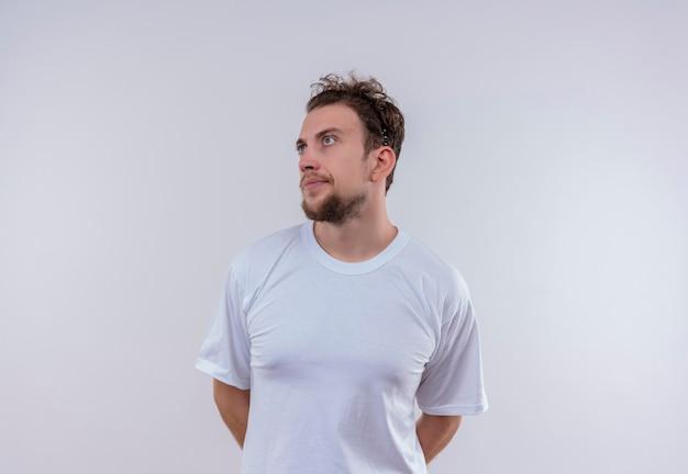 Auf die seite blickend erfreuter junger mann, der weißes t-shirt trägt, legte seine hände zurück auf isolierte weiße wand