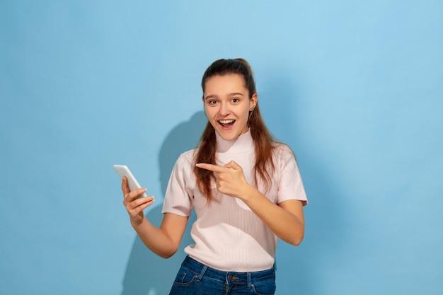 Auf ein smartphone zeigen und lächeln. porträt des kaukasischen jugendlich mädchens auf blauem hintergrund. schönes modell in freizeitkleidung. konzept der menschlichen emotionen, gesichtsausdruck, verkauf, anzeige. copyspace. sieht glücklich aus.