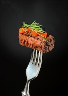 Auf eine gabel e wird ein saftiges stück fleisch mit ketchup und dill gepflanzt.