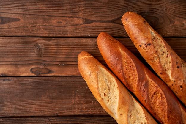 Auf einem alten holztisch liegen drei knusprige französische baguettes