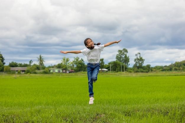 Auf einem biologisch angebauten reisfeld heben glückliche asiatische kinder beim springen ihre hände in den himmel und grinsen.