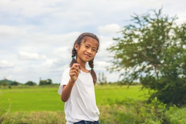 Auf einem biologisch angebauten reisfeld lächeln glückliche asiatische jugendliche in den himmel.