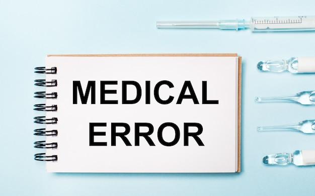 Auf einem blauen hintergrund ampulle mit medikamenten und einem notizbuch mit dem text medical error