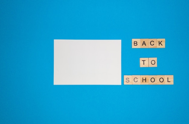Auf einem blauen hintergrund, ein notizbuchblatt und eine phrase aus holzbuchstaben, zurück zur schule, das konzept der rückkehr zur schule nach den ferien.