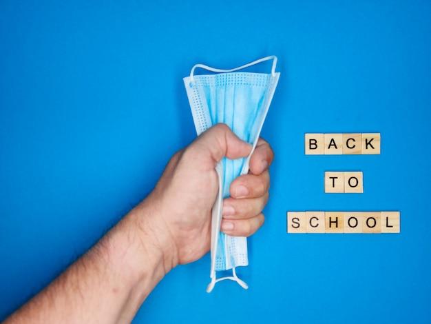 Auf einem blauen hintergrund, eine nahaufnahme einer hand, die eine medizinische maske und eine phrase aus holzbuchstaben umklammert, kopieren raum zurück. das konzept der rückkehr zur schule nach einer coronavirus-pandemie.
