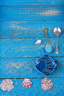 Auf einem blauen hölzernen hintergrund fisch, muscheln, löffel mit sand.