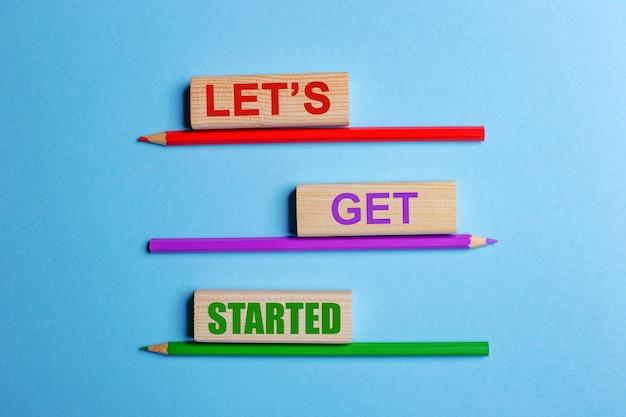 Auf einem blauen tisch drei buntstifte, drei holzklötze mit text lets get started