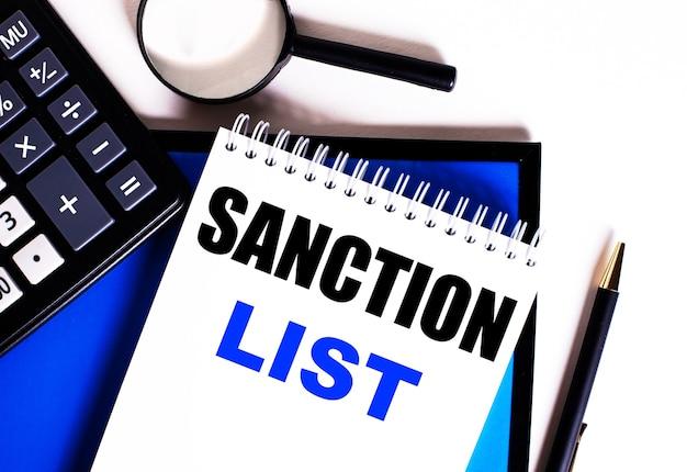 Auf einem blauen tisch neben dem taschenrechner, der lupe und dem stift ein notizbuch mit der aufschrift sanction list