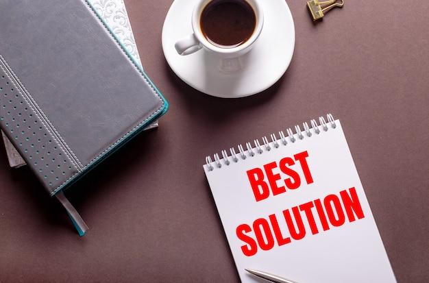 Auf einem braunen hintergrund tagebücher, eine weiße tasse kaffee und ein notizbuch mit best solution
