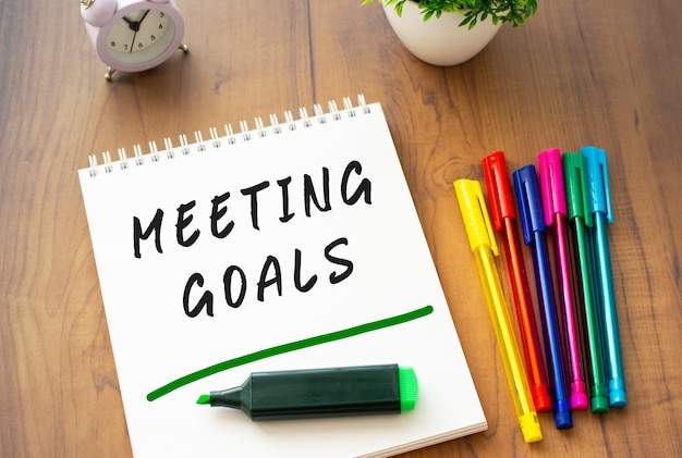 Auf einem braunen holztisch mit farbigen stiften liegt ein notizbuch auf einer feder mit dem text meeting goals auf einem weißen blatt. geschäftskonzept.