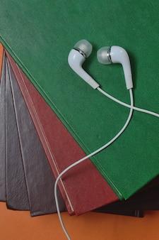 Auf einem bücherstapel liegen kleine weiße kopfhörer mit kabel. nahaufnahme