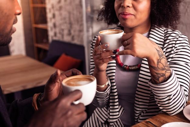 Auf einem date. nettes angenehmes paar, das zusammen kaffee trinkt, während es im café ist