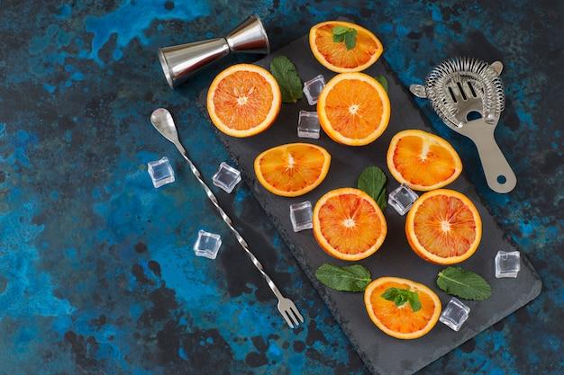 Auf einem dunkelblauen hintergrund orangen, eis, stücke für die zubereitung eines cocktails in stücke schneiden