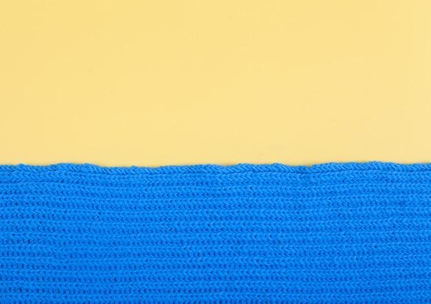 Auf einem gelben hintergrund liegt ein fragment eines von hand gestrickten blauen schals. handgemachtes konzept.